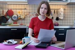 Durchdachtes betontes junges weibliches Sitzen am Küchentisch mit den Papieren und Laptop-Computer, die versuchen, durch Stapel v stockfoto