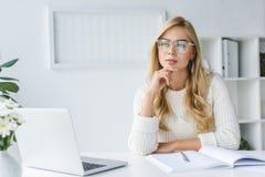 durchdachtes blondes Geschäftsfrau workig mit Laptop im modernen Licht Lizenzfreies Stockbild