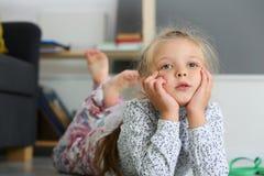 Durchdachtes blondes kleines Mädchen, das auf Boden liegt Stockfoto
