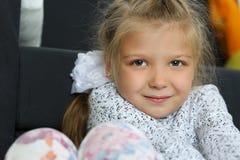 Durchdachtes blondes kleines Mädchen, das auf Boden sitzt Lizenzfreie Stockfotografie