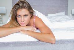 Durchdachtes blondes Lügen auf ihrem Bett Lizenzfreie Stockfotografie