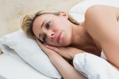 Durchdachtes blondes Lügen im Bett Stockbilder