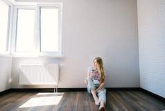 Durchdachtes blondes Mädchen, das in einem leeren Wohnzimmer sitzt Stockfotos