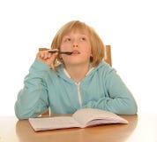Durchdachtes Mädchen, das am Schreibtisch sitzt Stockfotografie