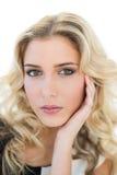 Durchdachtes blondes Modell, das ihren Tempel berührt Stockfotos