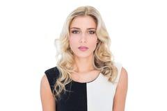 Durchdachtes blondes Modell, das Kamera betrachtet Stockbilder