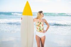 Durchdachtes blondes Modell im Badeanzug, der ein Surfbrett hält Stockfotografie