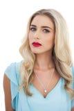 Durchdachtes blondes Modell im blauen Kleid, das Kamera betrachtet Lizenzfreie Stockfotografie