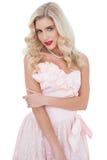 Durchdachtes blondes Modell im rosa Kleid, das ihren Arm halten aufwirft Stockbilder