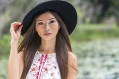Durchdachtes chinesisches asiatisches junge Frauen-Mädchen, das schwarzen Hut trägt Stockbild