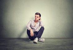 Durchdachtes denkendes Sitzen des jungen Mannes auf einem grauen Boden stockfoto