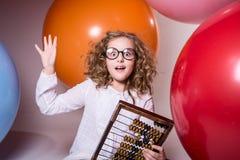 Durchdachtes gelocktes jugendlich Mädchen in den Gläsern mit hölzernem Abakus auf Stockfoto