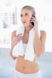 Durchdachtes junges blondes Modell, das mit ihrem Handy nennt Stockbilder