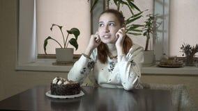 Durchdachtes junges Mädchen, das zu Hause nahe dem Kuchen am Tisch in der Küche sitzt, herum schaut und wartet stock video footage