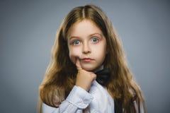 Durchdachtes junges Mädchen der Nahaufnahme, das oben mit der Hand dem Gesicht lokalisiert auf Gray Background betrachtet Stockfotografie