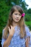 Durchdachtes junges Mädchen mit Blume im Haar Lizenzfreies Stockfoto