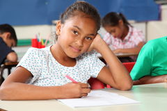 Durchdachtes junges Schulmädchen im Klassenzimmerschreiben Stockbild