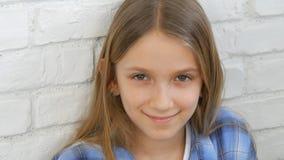 Durchdachtes Kinderporträt, lächelndes Kindergesicht, das in camera blondes gebohrtes Mädchen schaut stockfoto