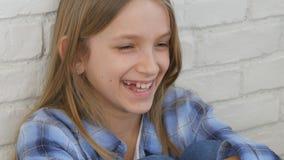 Durchdachtes Kinderporträt, lachendes Kindergesicht, das in camera blondes gebohrtes Mädchen schaut stockfotografie