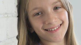 Durchdachtes Kinderportr?t, l?chelndes Kindergesicht, das in camera blondes gebohrtes M?dchen schaut stock video footage