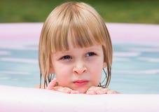 Durchdachtes kleines Mädchen im aufblasbaren Pool Lizenzfreies Stockbild