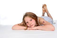 Durchdachtes Mädchen auf Magen Lizenzfreie Stockbilder