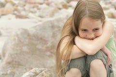 Durchdachtes Mädchen, das auf Felsen sitzt Lizenzfreies Stockfoto