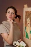 Durchdachtes Mädchen, das eine Abbildung malt Stockfotos