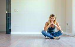 Durchdachtes Mädchen, das in einem Wohnzimmer sitzt stockbilder