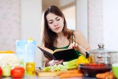 Durchdachtes Mädchen, das mit Kochbuch kocht Stockfotos