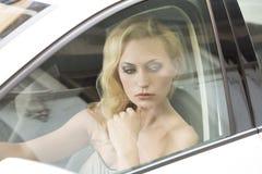 Durchdachtes Mädchen in einem Auto Stockfotografie