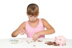 Durchdachtes Mädchen mit dem Sparschwein lokalisiert Stockbilder