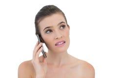 Durchdachtes natürliches braunes behaartes Modell, das einen Telefonanruf macht Stockfotos