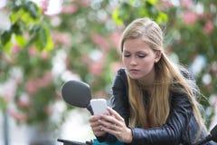 Durchdachtes nettes blondes Mädchen auf einem Roller unter Verwendung des Handys Lizenzfreies Stockfoto