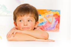 Durchdachtes Porträt des kleinen Jungen auf dem Tisch gelegt Stockbilder