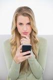 Durchdachtes recht blondes, einen Text sendend, der auf angenehmem Sofa sitzt Lizenzfreies Stockbild