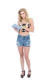 Durchdachtes Retro- blondes Modell, das einen Tabletten-PC hält Stockbild