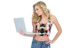 Durchdachtes Retro- blondes Modell unter Verwendung eines Laptops Stockbilder