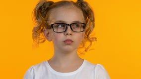 Durchdachtes Schulmädchen in den Gläsern, die versuchen, die Entscheidung zu treffen verkratzt ihr Kinn stock video footage