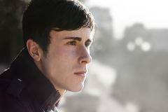 Durchdachtes Seitenporträt des jungen Mannes Stockbild