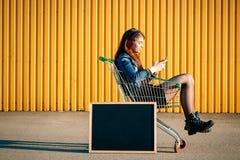 Durchdachtes stilvolles junges Mädchen in der Jeansjacke, -stiefeln und -rock, Stockfotos