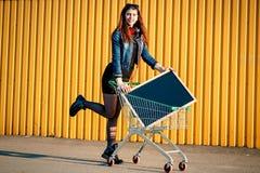 Durchdachtes stilvolles junges Mädchen in der Jeansjacke, -stiefeln und -rock, Stockbild