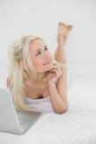 Durchdachtes zufälliges entspanntes blondes mit Laptop im Bett Stockfotografie