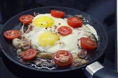 Durcheinandergemischte Eier, die in einer Bratpfanne, kochend auf einem keramischen Ofen, Spiegeleiern mit Speck und einer Tomate stockbild