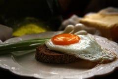 Durcheinandergemischte Eier mit Frühlingszwiebeln, Roggenbrot und Butter stockfotografie