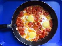 Durcheinandergemischte Eier mit Tomaten Stockfoto