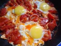 Durcheinandergemischte Eier mit Tomaten Stockbilder