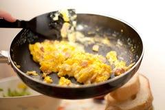 Durcheinandergemischte Eier und Speck in Metalldem schwarzen Kochen verschiebt italienisches Lebensmittel Stockbild