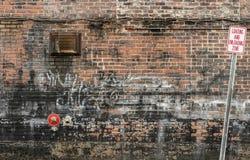 Durcheinandergeworfener alter Backsteinmauer-Hintergrund mit Graffiti und Zeichen 2 Lizenzfreies Stockfoto