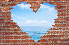 Durchlöchern Sie Formherz innerhalb der Backsteinmauer, Symbol der Liebe, Backsteinmauer h Stockbild